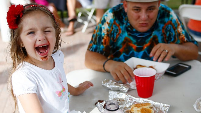 Bella Solis, 4, hams for the camera as her father, Robert, both of Naples laughs during the 2015 Taste of BOnita at Riverside Park in downtown Bonita Springs.