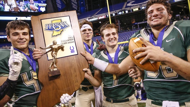 Westfield Shamrocks' team captains hold up their Class 5A state championship trophy after defeating the Columbus East Olympians 16-13 in the Class 5A state title game at Lucas Oil Stadium on Saturday, Nov. 26, 2016.