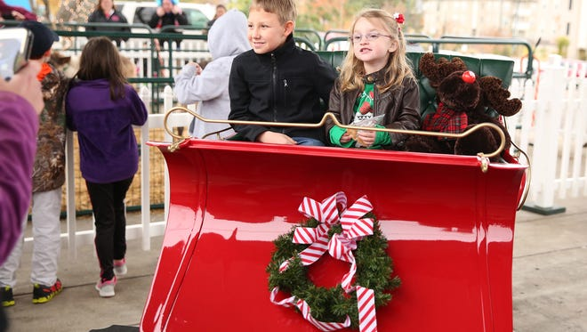 Phoebe Hughes, 4, and Conner Heddington, 11, pose in Santa's sleigh for photos Saturday at Jackson's Christmas in the City.