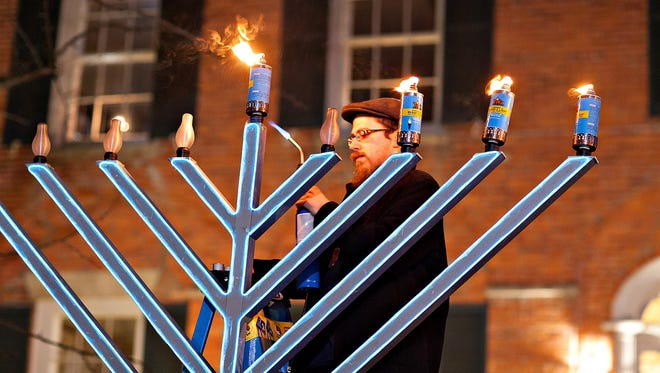 Rabbi Hein lights a menorah.