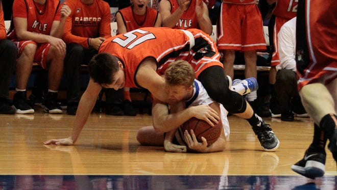 Travis Connley of Conner wrestles with Aaron O'Hara of Ryle over a loose ball on Friday, Dec. 16.