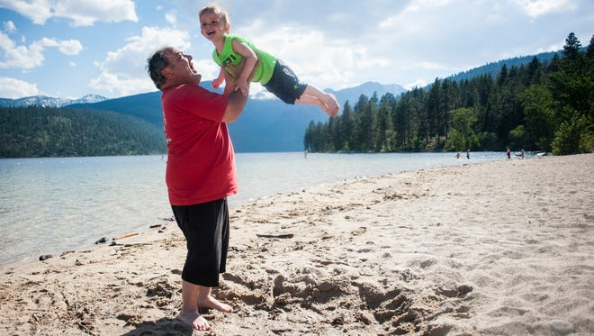 James Blackwell tosses his two-year-old grandson Ezekiel Blackwell into the air at the Lake Como beach in Ravalli County. He moved to Darby in 2009 so his children could go to school there.