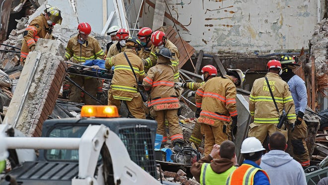 A woman is rescued from the rubble by emergency personnel on scene after the Copper Lounge building collapse Friday, Dec. 2, 2016, in downtown Sioux Falls.