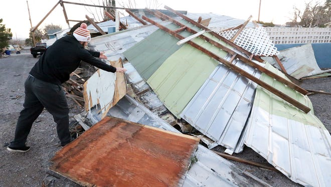 Josh Johnson of El Paso moves a piece of wood planking that fell into his neighbor's house after his carport collapsed from high winds in an alleyway along the 4700 block of Banner Court Saturday in Central El Paso. Power outages and roof damage were reported in various locations around town.