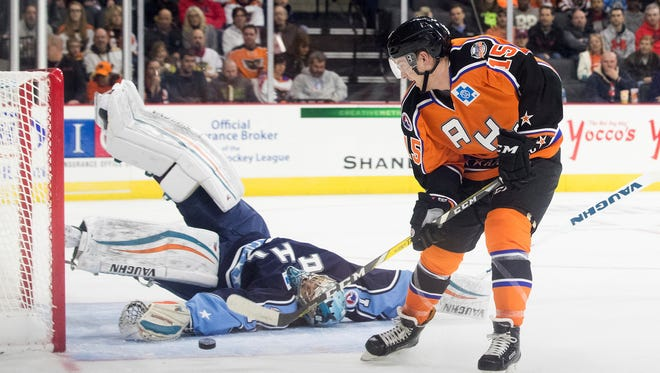 The AHL Pacific Division All-Star team goalie Troy Grosenick falls over as he blocks a shot by the Atlantic Division's Travis Boyd during an AHL All-Star Classic hockey championship game in Allentown, Pa., Monday, Jan. 30, 2017. (Christopher Dolan/The Citizens' Voice via AP)