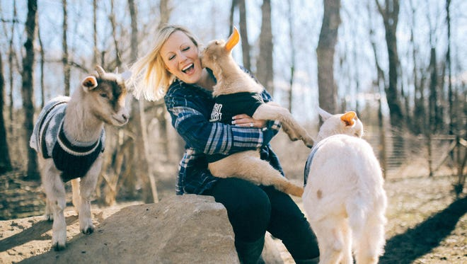 Leanne Lauricella poses for a picture with her goats.