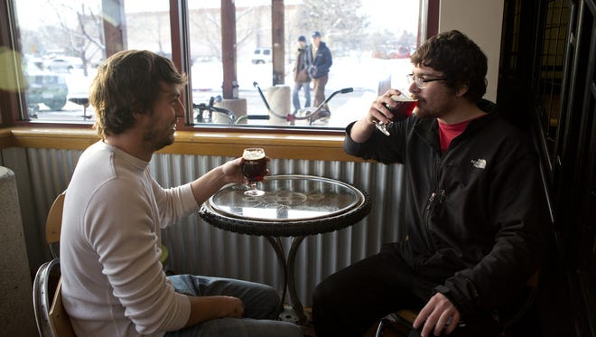 Nathan Westerfield, right, and Brandon Senn drink a couple of La Folie brews at the New Belgium Brewing Company tasting room in Fort Collins Friday, Feb. 7, 2014.