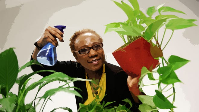 Watering plants gives Angela Peterson, Milwaukee Journal Sentinel photo editor, the opportunity to move around her workplace.