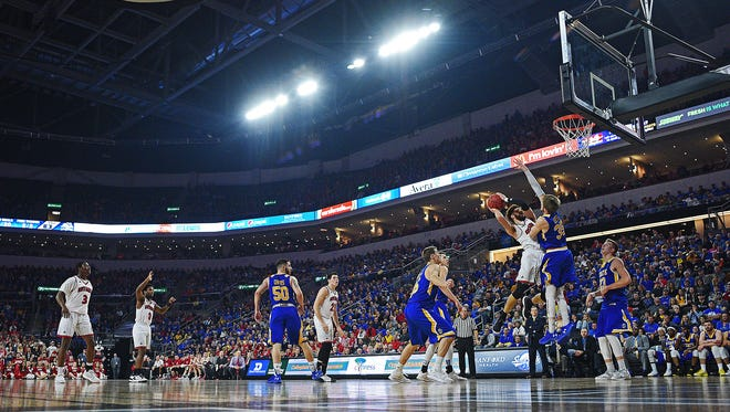 USD's Trey Burch-Manning (12) goes up for a shot as SDSU's A.J. Hess (35) defends during a Summit League Tournament semifinal game Monday, March 6, 2017, at the Denny Sanford Premier Center in Sioux Falls.