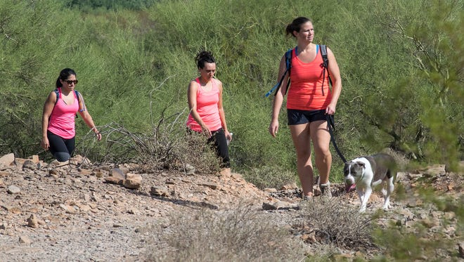 Starting from the North Mountain Park Visitors Center, hikers and a canine companion climb up a hill along a trail. Temperatures are expected to hit the mid-90s by Friday.