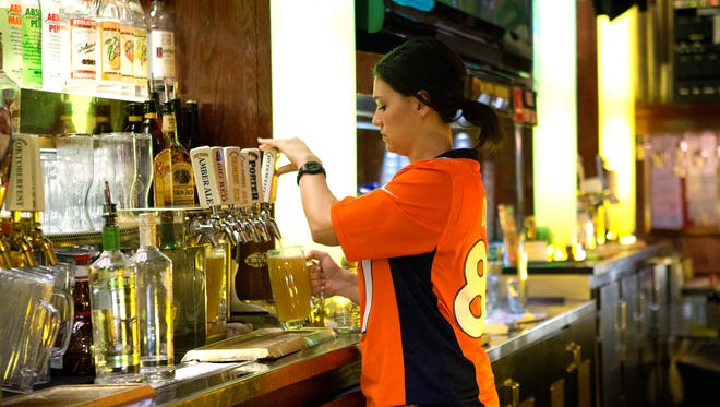 Bartender Rachel Witt pours beer at the original C.B. & Potts in Fort Collins in 2014. The brewpub chain announced it will temporarily halt brewing in Fort Collins.