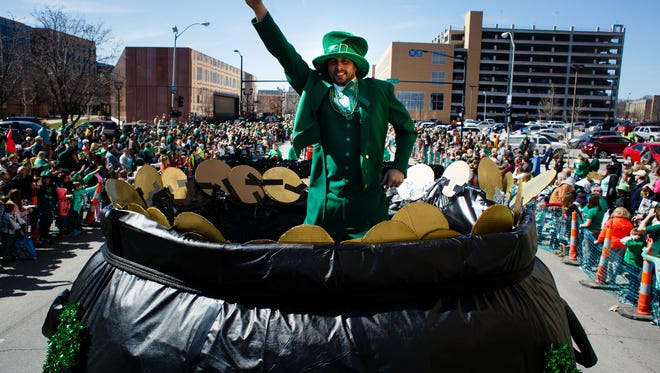 Dressed as a leprechaun, Tobit Bowles, jumps on a trampoline inside a pot of gold and waves as thousands line the streets for the annual St. Patrick's Day parade on Friday, March 17, 2017, in Des Moines.