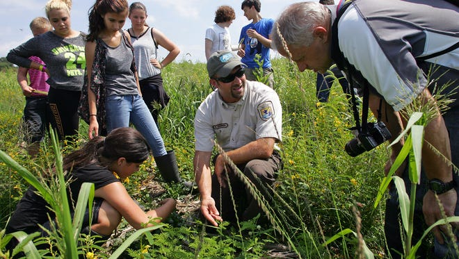Jim Reding, right, seen with Brent Sodergren, center, a fish and wildlife biologist for the U.S. Fish and Wildlife Service, and students at the land lab site in 2014..