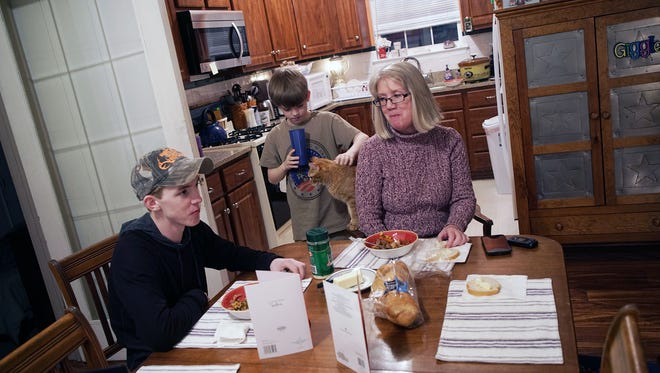 Pat eats dinner with her grandsons who she has been raising since the courts awarded her full custody after her son and daughter-in-law could not properly care for them because of a heroin addiction.