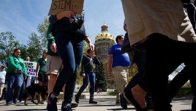 People take part in the March for Science make their way around the capitol building on Saturday, April 22, 2017, in Des Moines.