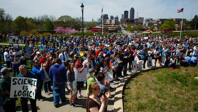 People taking part in the March for Science listen to speakers before making their way around the capitol building on Saturday, April 22, 2017, in Des Moines.