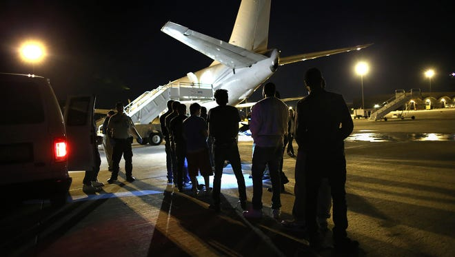 Undocumented immigrants wait to be loaded onto an Immigration and Customs Enforcement charter jet early on Oct. 15, 2015, in Mesa, Ariz. The immigrants were to be flown to other states for follow-on ICE deportation flights to the Caribbean, Mexico and Central America.