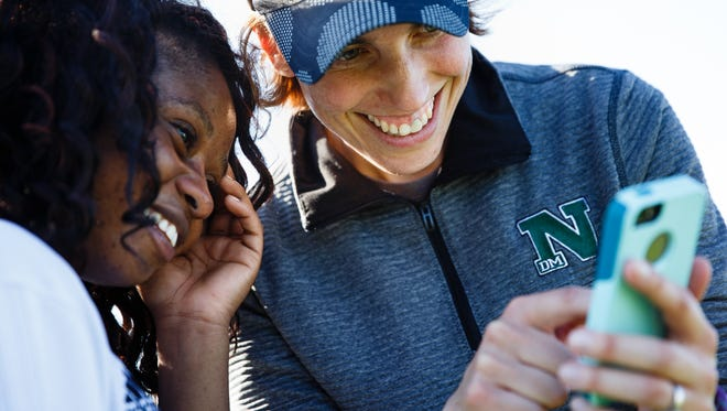 Coach Lisa Grefe shows senior Lea Kipendo a photo she took of her in preparation for senior night after the team defeated East 4-3 on Friday, May 12, 2017, in Des Moines.