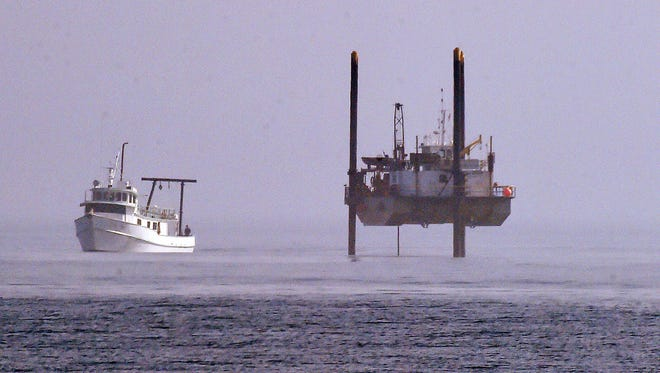 A large offshore drilling rig and survey boat take soil samples from the seabed where the Atlantic Ocean is about 15 feet deep as part of engineering work for the Rehoboth Beach sewage outfall pipe.
