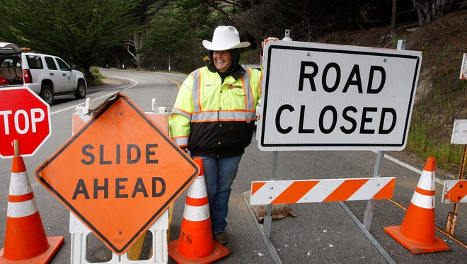 Arleen Guzzie works the road block at Ragged Point on Highway 1 stopping traffic from traveling toward the Mud Creek slide in southern Monterey County on the coast in Big Sur.