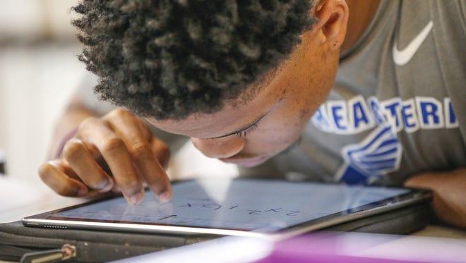 """نوح مالون يعمل في غرافيتي خلال حصة ليزا ستورفيلد للرياضيات في مدرسة إنديانا للمكفوفين والمكفوفين. """"الأشياء التي يسهل على المكفوفين الوصول إليها ، تستغرق وقتًا طويلاً للقيام بذلك ،"""" هو يقول."""