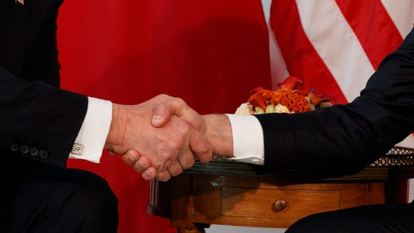 President Donald Trump shakes hands with French President