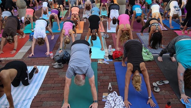 Yogis hold downward dog during Monumental Yoga, celebrating the Summer Solstice and National Yoga Day on Monument Circle, downtown Indianapolis, Wednesday, June 21, 2017.