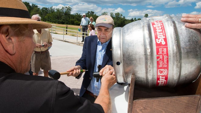 """Retired Glendale City Administrator Richard Maslowski (center) swings the mallet to tap the """"firkin"""" keg of beer, with help from Randy Sprecher (left), as the city of Glendale and neighbors celebrated the opening of the Richard Maslowski Community Park June 24, 2017. Sprecher plans to hold its first-ever Root Beer Bash at the park on Aug. 26."""