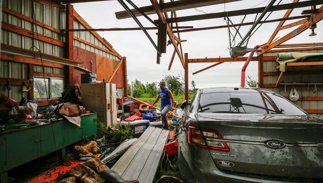 Dalton Noonan looks through debris to find a tool to fix a chain saw as he cleans storm damage at Justin Plein's home in Prairieburg Thursday, June 29, 2017.