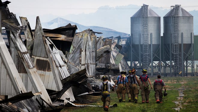 Firefighters work at the scene of a massive blaze inside a Hillendale Farms chicken house on the 3700 block of Oxford Road on Saturday, July 1, 2017 in Tyrone Township. Over 110,000 chickens perished in the fire, said Heidlersburg Fire Chief Dwayne Keene, and two firefighters received minor injuries while fighting the blaze.