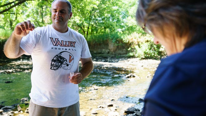 Valley High School chemistry and physics teacher Marc Pedersen, left, works with Ginny Malcomson of the Polk County Conservation Water Quality Program to test water July 20 in Windsor Heights.