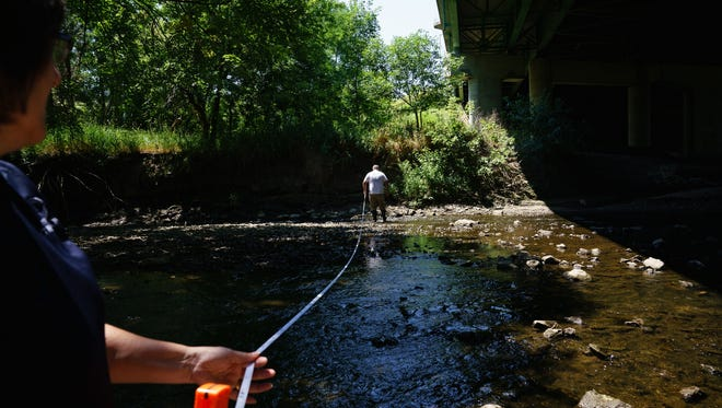 Valley High School Chemistry and Physics teacher Marc Pedersen walks a measuring tape across Walnut Creek to measure its width as Ginny Malcomson of the Polk County County Conservation Water Quality Program holds the other end in Colby Woods on Thursday, July 20, 2017 in Windsor Heights.