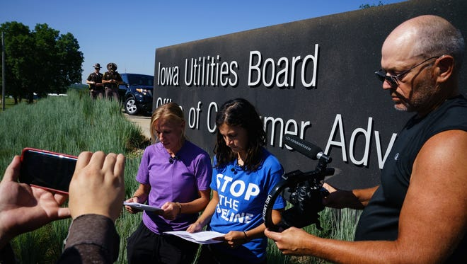 Jessica Reznicek, left, and Ruby Montoya, right, admit to previously vandalizing Dakota Access equipment infront of the Iowa Utilities Board on Monday, July 24, 2017 in Des Moines. The pair finished their statement and then pried off letters from the sign before being arrested by the Iowa State Patrol.