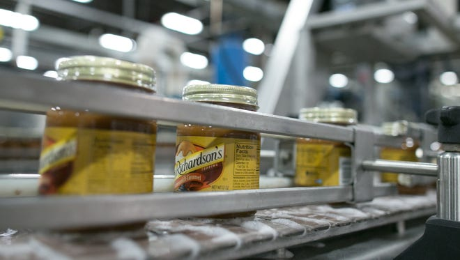 File photo: Newly labeled jars of Mrs. Richardson's Butterscotch Caramel topping move down the conveyor at Baldwin Richardson Foods in Macedon in 2015.
