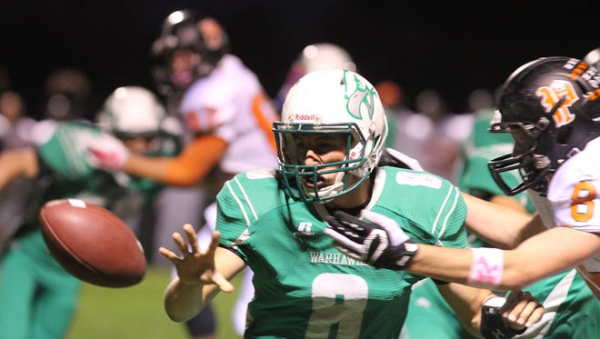 Southeast Warren senior pitches the ball on an option play as Pleasantville senior Ethan Worthington closes in. Southeast Warren hosted Pleasantville for their Homecoming game Oct. 9, 2015 in Lacona.
