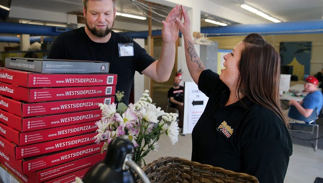 Angelique Easton, right, a line cook at Westside Pizza, drops off pizzas with Kitsap Rescue Mission shelter manager Nate Sylling on Tuesday.
