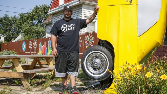 Danny Marquez, who leads Youth for Christ's Near Westside chapter of City Life, poses next to a 1964 Bonneville, which stands as an artistic ode to the Mexican culture in the area, at the Purpose Park, 58 N. Holmes Ave.