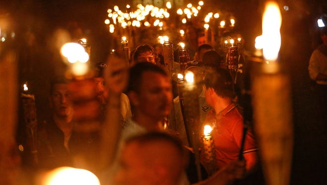 Multiple white nationalist groups march with torches through the University of Virginia campus in Charlottesville on Friday, Aug. 11, 2017. Ryan Roy, 28, of Burlington, Vt., was recorded in a Vice News documentary carrying a torch. Roy was fired from his job at Uno Pizzeria and Grill in South Burlington, Vt., on Tuesday, Aug. 15, 2017.