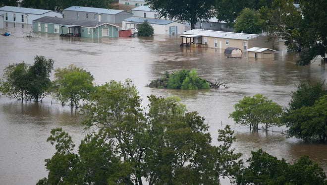 A trailer park is flooded in La Grange, Texas, Monday, Aug. 28, 2017, after floodwaters from Tropical Storm Harvey inundated the area. Floodwaters reached the rooflines of single-story homes Monday and people could be heard pleading for help from inside as Harvey poured rain on the Houston area for a fourth consecutive day after a chaotic weekend of rising water and rescues. (Ralph Barrera/Austin American-Statesman via AP)