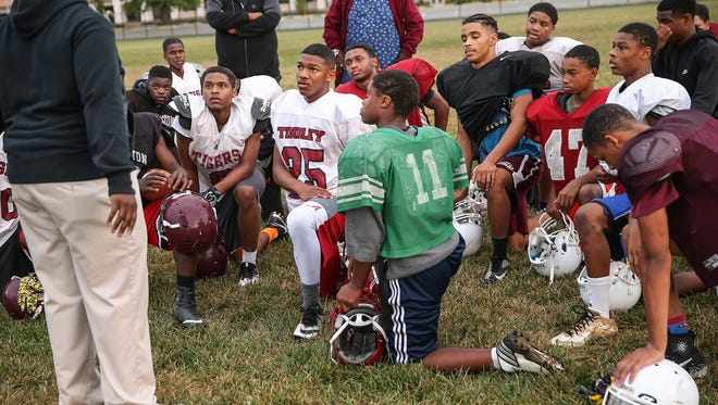 The Tindley Tigers listen to coach Chris Edison during practice at Charles A. Tindley Accelerated School, Indianapolis,Wednesday, Sept. 13, 2017. The team of only 15 varsity players is off to a 4-0 start.
