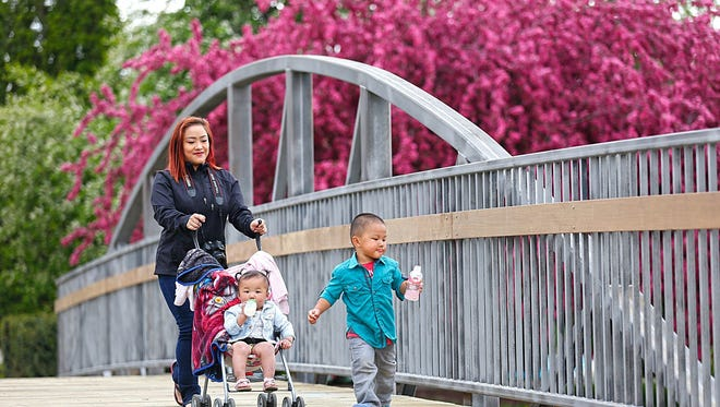Doug Raflik/USA TODAY NETWORK-Wisconsin Lilly Lee, Evelyn and Aiden Xiong of Sheboygan walk across the new walking bridge in Lakeside Park in Fond du Lac. Lilly Lee, Evelyn and Aiden Xiong of Sheboygan walk across the new walking bridge in Lakeside Park.