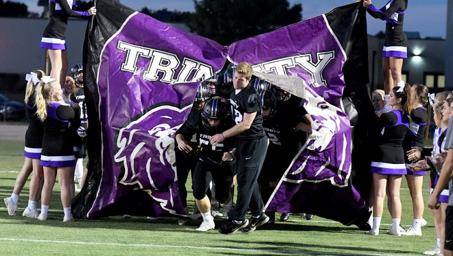 Trinity Christian's Zach Yarbrough leads his team out through the banner before the start of their game against Union City, Friday, September 29.