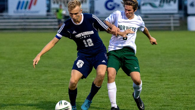 East Lansing's Alden Metzmaker, left, and Williamston's Evan Rugh battle for position during the first half on Tuesday, Sept. 3, 2017, in Williamston.