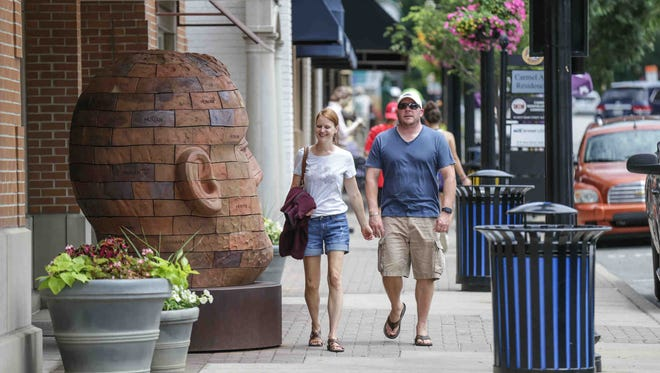 A couple strolls past a sculpture in downtown Carmel Indiana on Thursday June 15, 2017.