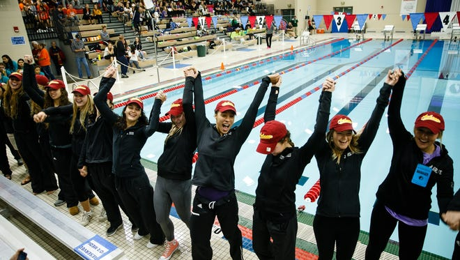 Jasmine Rumley, center, cheers with the rest of the Ankeny swim team during the parade before the Iowa high school girls state swimming meet on Saturday, Nov. 4, 2017, in Marshalltown.