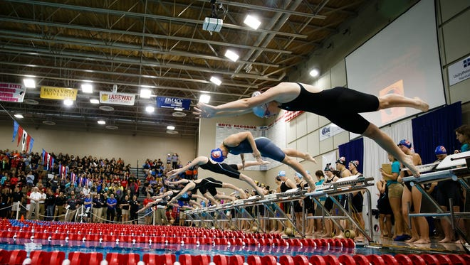 Swimmers dive into the pool for the second heat of the 400 yard freestyle relay at the Iowa high school girls state swimming meet on Saturday, Nov. 4, 2017, in Marshalltown.