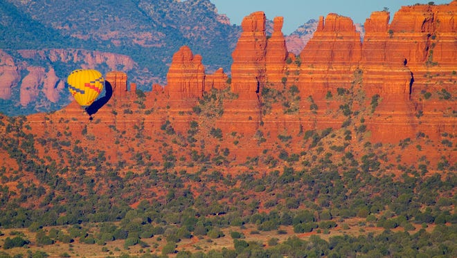 Hot air balloons lift off in the early morning to greet the sunrise above the red rocks.
