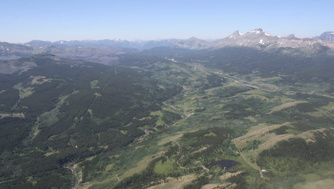 This June 16, 2015 aerial photo, shows the Badger-Two Medicine area near the Blackfeet Indian Reservation and Glacier National Park, rear, in Montana.
