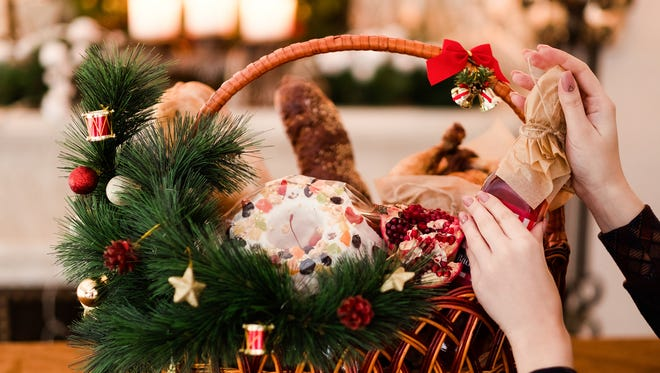 A holiday gift basket is filed with fruitcake, fresh fruit and dried sausages.