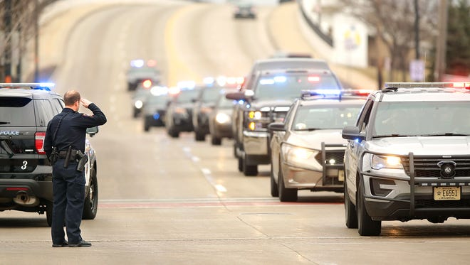 A City of Fond du Lac Police Officer salutes a procession of police cars from Fond du Lac and Marathon counties in honor of Detective Jason T. Weiland of the Everest Police Department who was killed by a gunman March 22 in Marathon County.